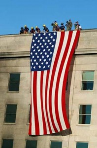 010912-N-3235P-003 Arlington. Va. (Sept. 13, 2001) -- Military servicemembers render honors as fire and rescue workers unfurl a huge American flag over the side of the Pentagon during rescue and recovery efforts following the 11 Sept. terrorist attack. The attack came at approximately 9:40 a.m. as a hijacked commercial airliner, originating from Washington D.C.'s Dulles airport, was flown into the southern side of the building facing Route 27.  U.S. Navy photo by Michael W. Pendergrass.  (RELEASED)